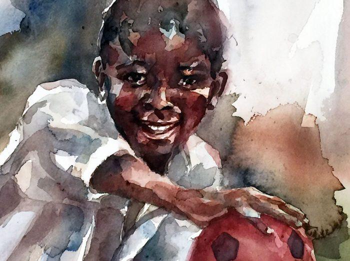 Niño negro con una pelota roja sonriendo